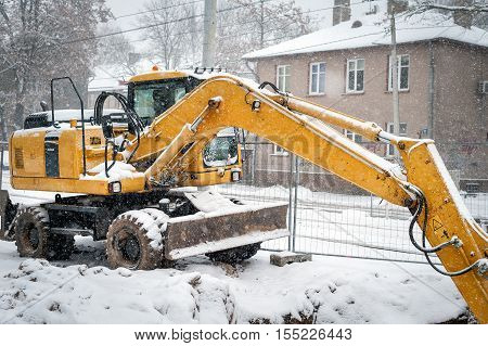 Yellow excavator covered by snow at winter construction site