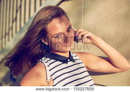 Close up portrait of happy beautiful girl talk by mobile and look to the camera. Interesting woman in dress walking in the city. Copy space for advertising text.