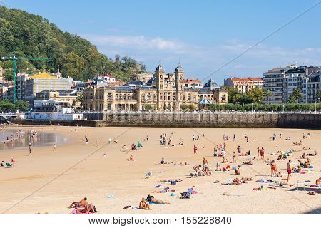 SAN SEBASTIAN, SPAIN  - SEPTEMBER 30. The Beach of La Concha, one of the most famous urban beaches in Europe. In the background the city hall, the former casino of San Sebastian on September 30, 2016