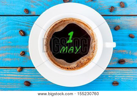 May 1st. Day 1 of month, calendar written on morning coffee cup at blue wooden table, Top view. Spring time.