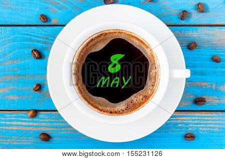 May 8th. Day 8 of month, calendar written on morning coffee cup at blue wooden table, Top view. Spring time.