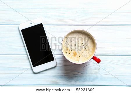 Cup Of Coffee And Smarphone On A Blue Wooden Table