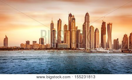 Beautiful Dubai cityscape, panoramic view of the modern city on the bank of gulf in sunset light, famous touristic place, United Arab Emirates