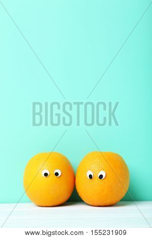 Ripe Oranges With Googly Eyes On Green Background