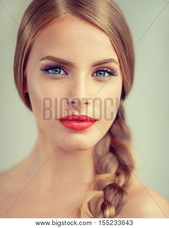 Beautiful  brunette model girl with  long braid hair . Hairstyle  pigtail  . Orange lips .