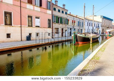 boat in a canal of the colorful italian village of Comacchio in Emilia Romagna Italy