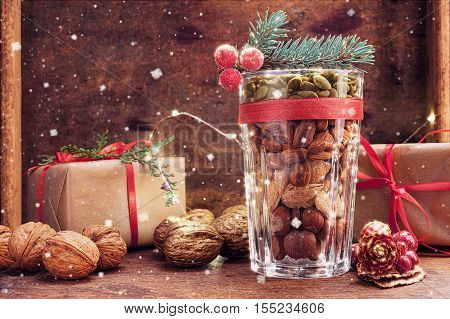 Christmas decoration glass with a variety of nuts on a wooden background with flying snow and copy space