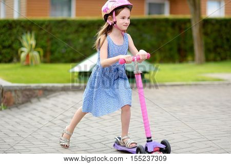 Adorable Little Girl Riding Her Scooter In A Summer Park