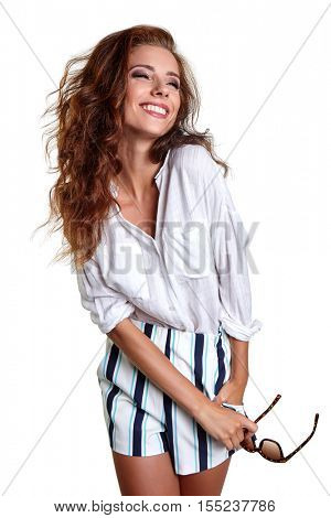 smiling young slim tanned female in denim shorts shrugging her shoulders, isolated on white background