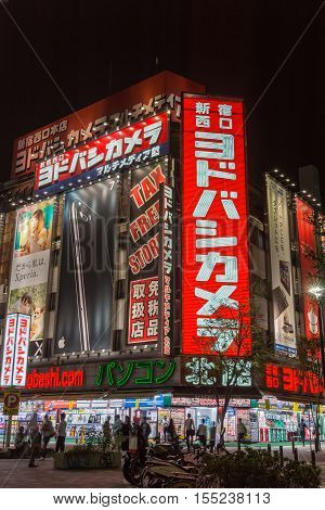 Tokyo Japan - September 29 2016: Night photo of a corner at an intersection near Shinjuku Station. Giant electronics store with bright neons covering the entire facade. People and black sky.