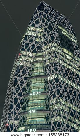 Tokyo Japan - September 29 2016: Night photo of the top half of the Cocoon building officially Tokyo Mode Gakuen. Sections lighted metal frame with lots of triangles and a black sky.