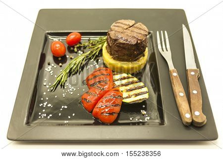 Mignon steak with fried potatoes and grilled vegetables on a beautiful black plate with knife and fork on a white background