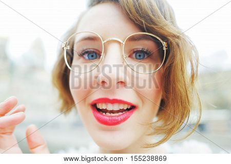 Portrait of funny beautiful smiling the girl bespectacled closeup.