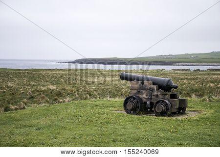 shooting cannon at Orkney coastline cliff landscape