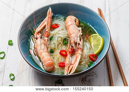 Traditional Thai soup with scampi on old wooden table