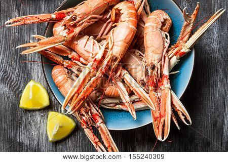 Cooked scampi served with lemon on old wooden table