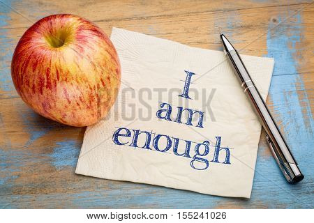 I am enough positive affirmation - handwriting on a napkin with a fresh apple
