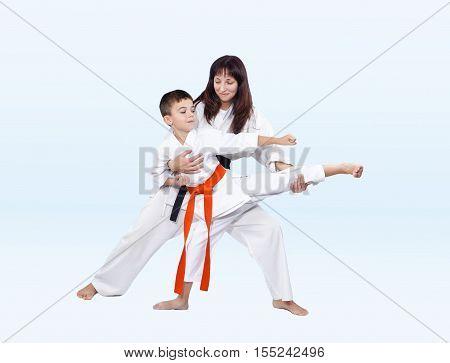 Karateka beats kicking trainer corrects on the light background