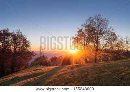 Autumn landscape in a mountain village. Beautiful sunset with a warm glow. Stacks dry hay in a meadow. Subsistence agriculture. Carpathian, Ukraine, Europe. HDR and color toning
