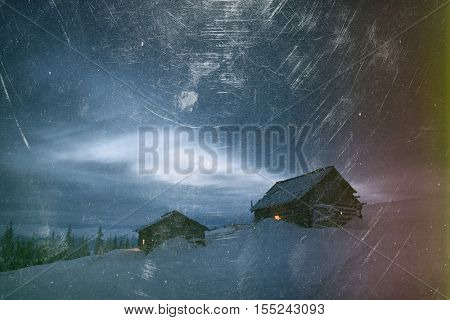 Night landscape. Winter in mountain village. Light in windows of wooden houses. Path in snow. Effect of old photos from scuffs and scratches