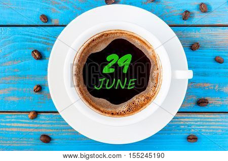 June 29th. Day 29 of month, everyday calendar written on morning coffee cup at blue wooden background. Summer concept, Top view.