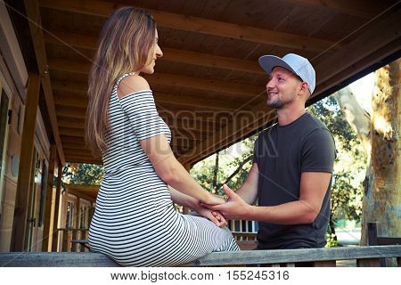 Close-up of a handsome bearded man who is holding hands of his wife during the romantic conversation on the terrace. Caucasian brunette is sitting on the handrail and holding hands of her husband.