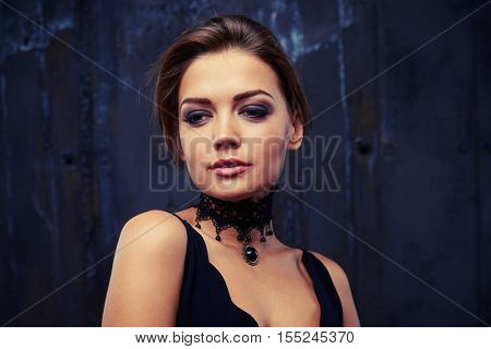 Close-up portrait of delighted pretty female with mouth open slightly and languishing look while posing at the camera. The combination of two colours of powder eyeshadow