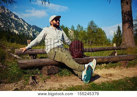 Mid side shot of bearded male who is sitting on the wooden bench. Stretches hands on the bench and admiring the view. Wearing casual comfortable clothes, with a leather brown rucksack