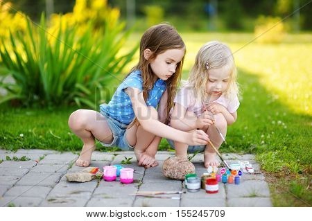 Two Cute Little Sisters Painting On Stones Together