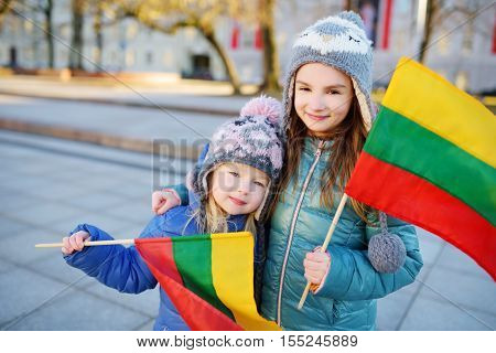 Two Adorable Little Sisters Holding Lithuanian Flags In Vilnius