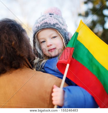 Father and daughter with a flag on Lithuanian independence day holding tricolor Lithuanian flag