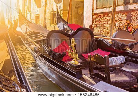 Docked venetian gondolas under bright sunlight Venice Italy. Gondola is a very popular kind of entertainment in Venice.