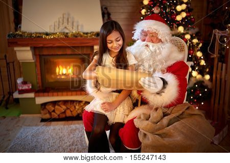 Little Asian girl in Santa Claus lap showing her wish on wish list