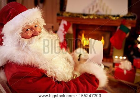 Santa Claus enjoy in warm home near the fireplace and reading wish list