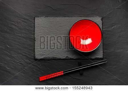 Two Chopsticks And Red Plate On Black Stone Background With Copyspace, Top View