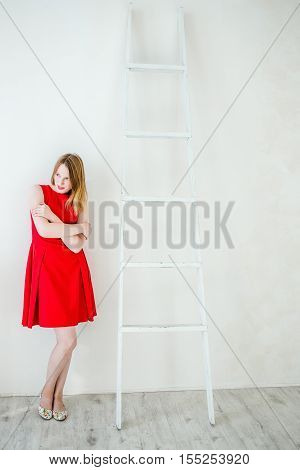 A woman with crossed hands in a red dress is standing near the ladder and looking away.