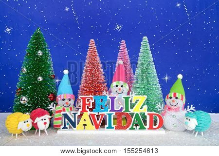 Feliz Navidad Merry Christmas in Spanish colorful wood sign red pink green pine trees with snowman and colorful yarn sheep on faux snow blue background white dots and stars.