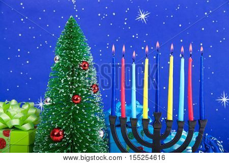 Miniature Christmas tree with presents next to Jewish menorah celebrating Hanukkah. Multi faith families celebrate both which are the same day this year December 25th