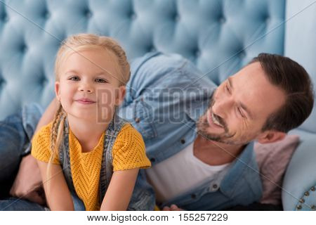 Being happy. Nice cute little girl sitting on the couch and smiling while spending time with her dad