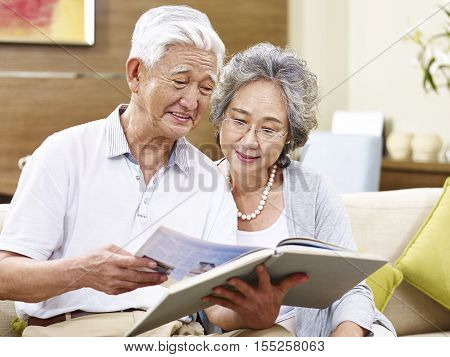 senior asian couple sitting on couch reading a book together