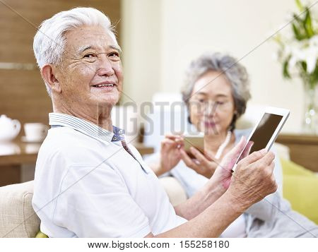 senior asian couple sitting on couch enjoying modern technology using tablet computer and cellphone
