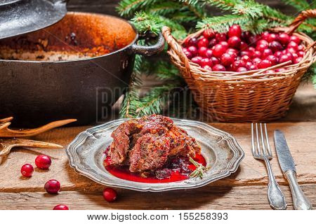 Roast venison with cranberry sauce on old wooden table