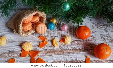 Tangerine macarons in jute sack and Christmas tree decorations on old wooden background
