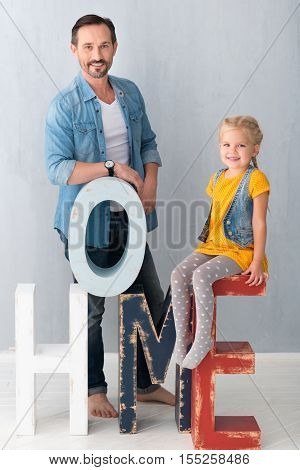 Wooden letters. Cute nice blonde girl sitting on the wooden letter E and smiling while spending time with her father