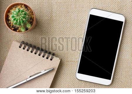 Touch screen smartphone with black screen and notebook on table / can be used for your text or artwork / Top view