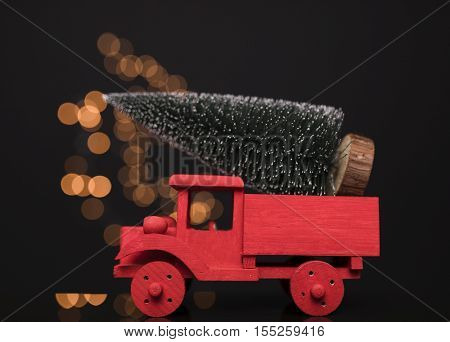 Red truck carrying a pine tree against black background