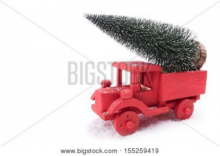 Red truck carrying a pine tree on the snow
