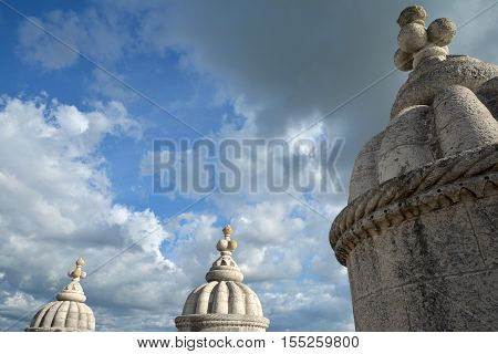 Beautiful cloudy sky seen through Belem Tower Manueline style pinnacles in Lisbon