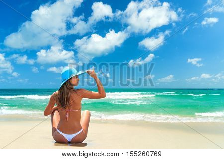 woman relaxing sitting in sand enjoying tropical beach destination.