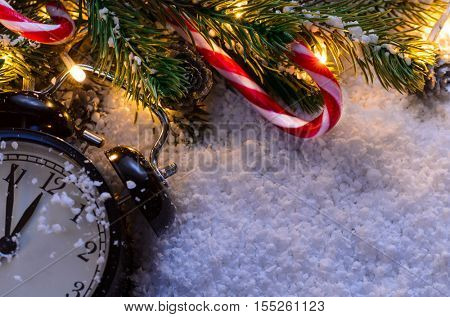 Christmas fir tree with lights and clock on snow in dark, view from above
